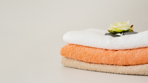 close-up-folded-clean-towels-with-flower_23-2148230615